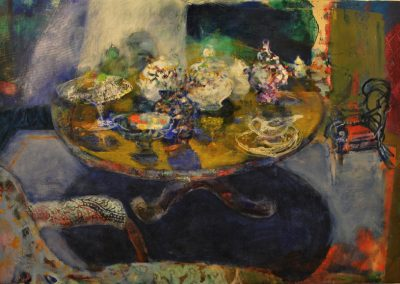 A table is laden with white crockery and fruit. there is a chaise-longue in the foreground