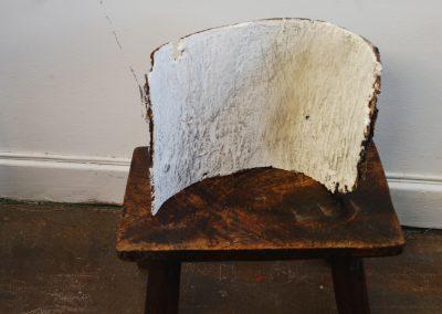 a bark sculpture on a milking stool