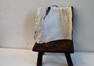 a bark sculpture on an milking stool